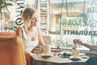 canvas print picture - International students are italkng while having coffee break in a cafe with modern interior. women freelancer is speaking with a friend about business ideas while drinking tea in a coffee shop