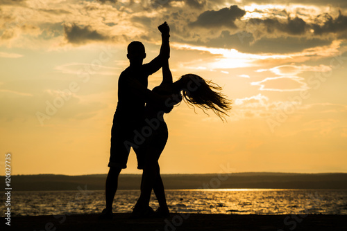 Poster Dance School Couple dancing at sunset salsa / brazilian zouk. Lovers, dance partners spinning, latin festival dance concept.