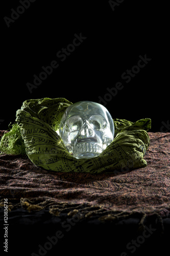 Plakát Mysterious glowing crystal skull on a black background