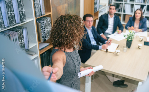 Obraz Female coach explaining project to business team in headquarters - fototapety do salonu