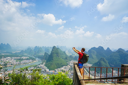 Cadres-photo bureau Guilin Hiker with backpack take a picture on his smartphone from top of the hill with beautiful view on Yangshuo city with mountains around. Yangshuo, China