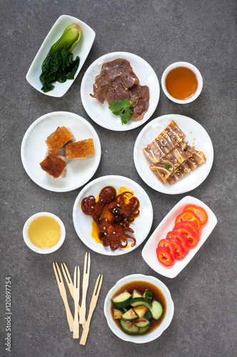 Fotografie, Obraz  Assorted Asian appetizers on white plates:  octopus in spicy sauce, sliced beef shank, pigs ears, crispy barbecue pork