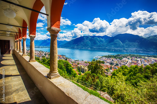 Fotografie, Obraz Beautiful view to Locarno city, lake Maggiore (Lago Maggiore) and Swiss Alps from Madonna del Sasso Church in Ticino, Switzerland
