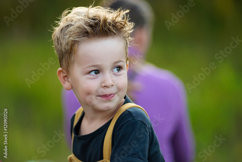 Valokuva  Cute little boy with tousled hair looking aside and smiling