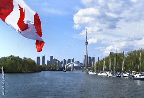 Spoed Foto op Canvas Canada Beautiful Canada flag is waving front of famous Toronto City view