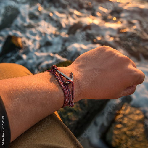 Fotografía  Male hand with silver anchor bracelet on ocean beach rocks.