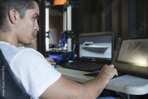 Designer using computer app while working with 3D printer