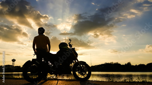 Fotobehang Motorsport Silhouette biker with his motorbike beside the natural lake and beautiful sunset sky.