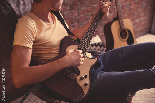 Young man playing guitar and sitting on chair in a room Wallpaper Mural