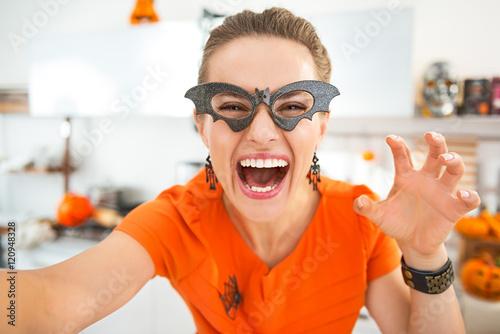 Fotografia, Obraz  happy young woman in Halloween decorated kitchen taking selfie