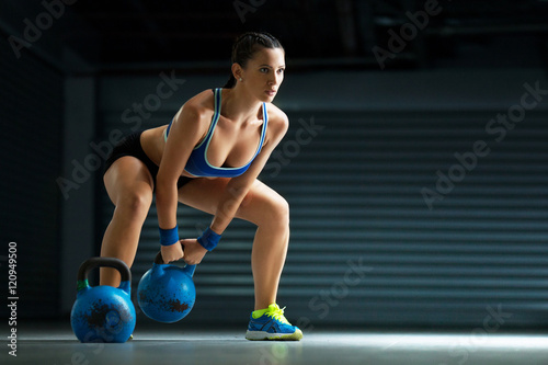 Young fit woman has cross fit training by kettle bell.