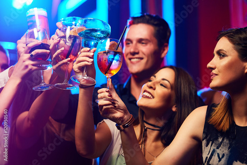 Tableau sur Toile Portrait of joyful friends toasting at party in the club