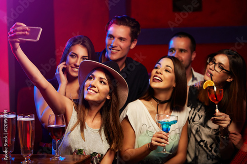 Fotografie, Obraz  Group of young smiling people taking selfie in the club or bar