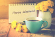canvas print picture - blue cup of coffee on wooden floor with yellow flower in white pot and happy weekend note on morning sunlight. vintage color tone, happy weekend concept.