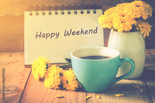 Fotografía  blue cup of coffee on wooden floor with yellow flower in white pot and happy weekend note on morning sunlight