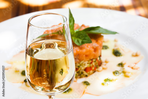 Fotografía Glass of sherry jerez, pink salmon fish tartar plate background, soft focus phot