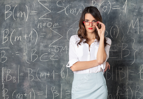 young smart sexy woman in eyeglasses near blackboard with math calculations