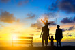 Silhouette family mother, father and young son holding hands, ta