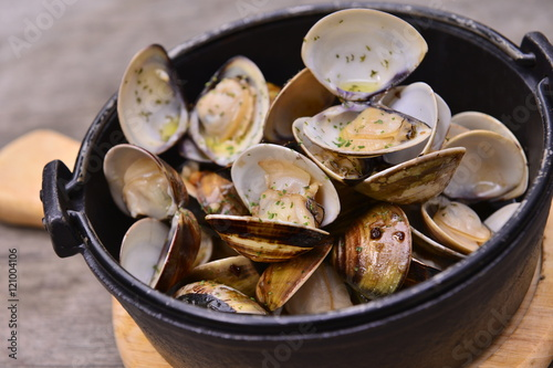 Photo  Garlic white wine clam in black pot on wooden tray in asian rest