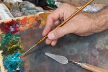 Male Hand Holding Paint Brush