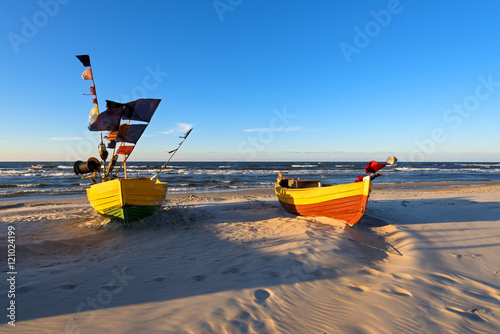 Foto op Aluminium Koraal Traditional fishing boats on sandy beach in Jantar village at sunset time. Baltic sea, Poland.