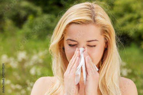 Valokuva  Unhappy woman with paper napkin sneezing.
