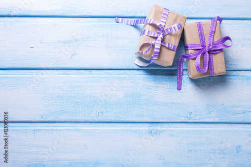 Two gift boxes with presents on blue painted wooden background.