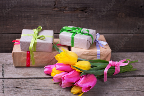 Photo  Bright yellow and pink spring tulips and wrapped  boxes with pre