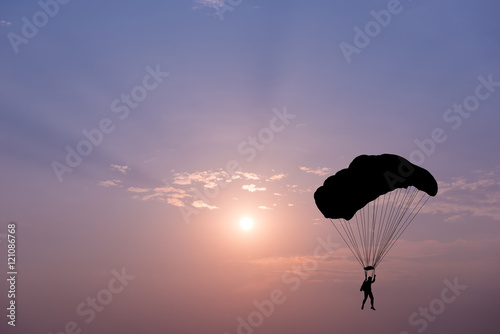 Poster Luchtsport Silhouette of parachute on sunset background
