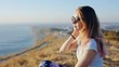 Beautiful girl with a sunglasses at the cliff above the sea. Beautiful girl enjoying a view at the cliff above the sea. Young woman relaxing on the beach.
