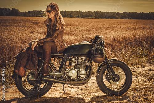 Obraz na plátně  Stylish woman on the vintage custom cafe racer in a field.