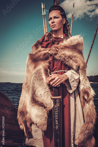 Photo  Viking woman with sword and shield standing on Drakkar.