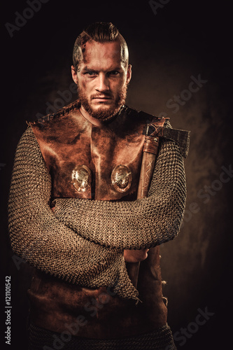 Photo  Angry viking in a traditional warrior clothes, posing on a dark background