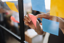 Hands Of Woman Sticking Adhesive Notes On Glass