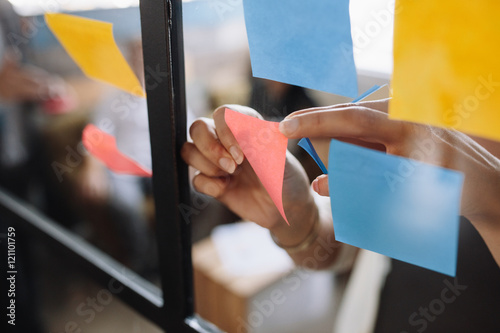 Obraz Hands of woman sticking adhesive notes on glass - fototapety do salonu