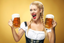 Young Sexy Oktoberfest Waitress, Wearing A Traditional Bavarian Dress, Serving Big Beer Mugs On Blue Background.