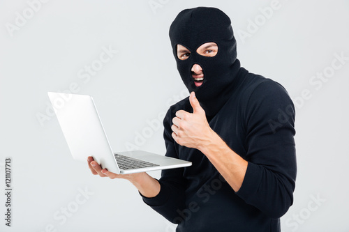 Photo Man in balaclava using laptop and showing thumbs up