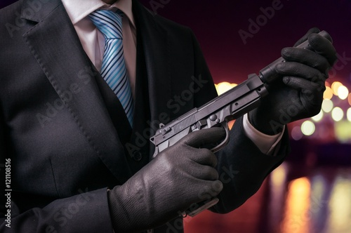 Photo  Murderer or killer holds pistol with silencer in hands at night.