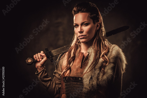 Photo  Viking woman with sword in a traditional warrior clothes, posing on a dark background
