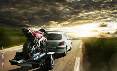 Plakat Wyścig motocykl na przyczepie za samochodem
