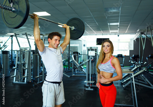 Athletic man and woman with barbell doing exercises in the gym