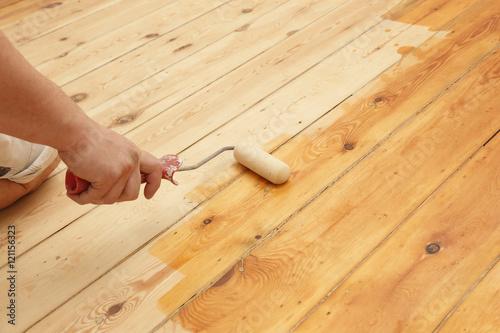 Obraz homme mettant huile de protection sur plancher au rouleau - fototapety do salonu