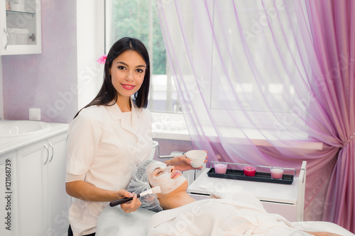 Photo  Cheerful young cosmetologist applying mask on female face with a brush