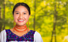 Headshot Beautiful Young Woman Wearing Traditional Andean Blouse With Red Necklace, Posing For Camera Touching Face Using Hands While Smiling Happily, Green Forest Background