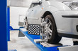Car on stand with sensors wheels for alignment camber check in workshop of Service station.