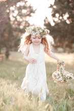 Laughing Baby Girl 4-5 Year Old Running In Meadow Holding Basket With Flowers Outdoors. Happiness. Childhood.
