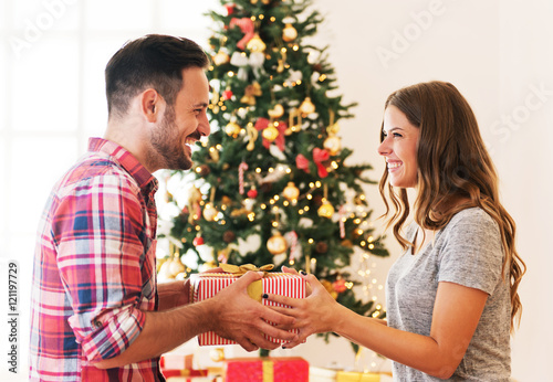 cute young couple exchanging christmas presents on christmas morning