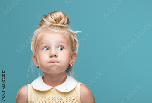 Obraz Small, young, funny girl, inflated cheeks on blue background - fototapety do salonu