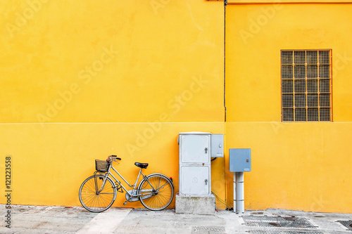 Classic bicycle standing over wide yellow wall.