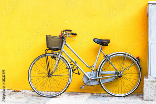 Old style bicycle parked against yellow wall.